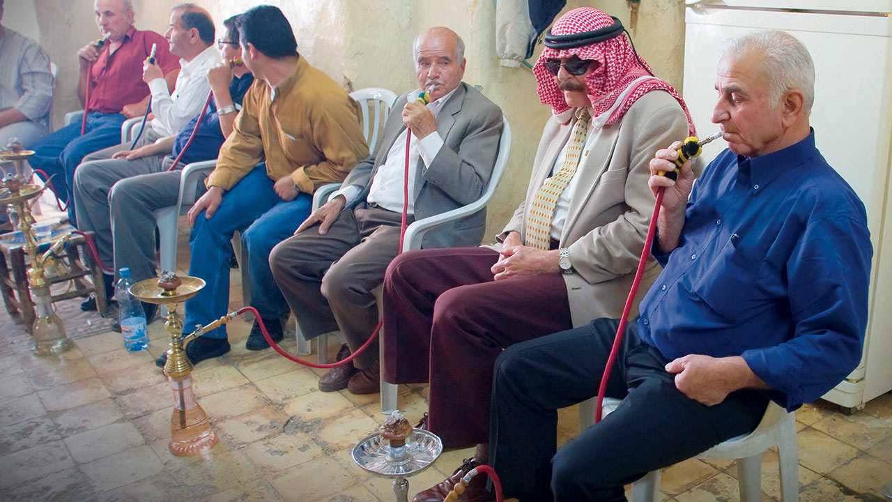 Local Arabs in a Palestinian town gather in a cafe to smoke flavored tobacco in Nargillas